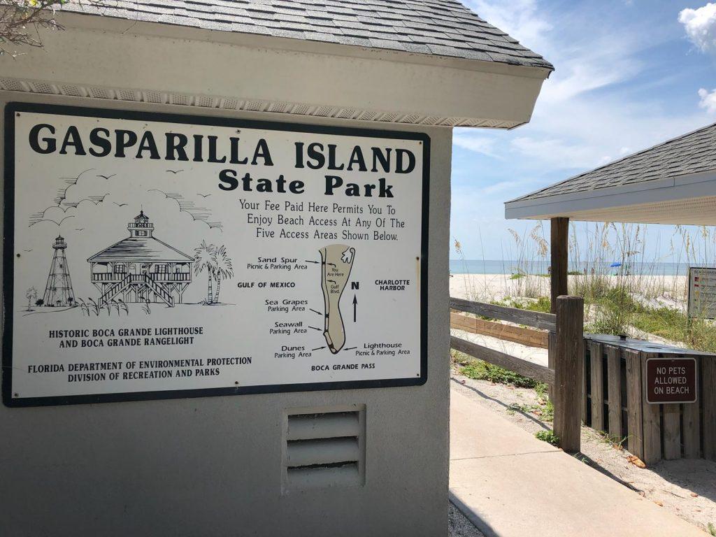 Anzeigentafel des State Parks von Gasparilla Island in Florida im Hintergrund der Strand
