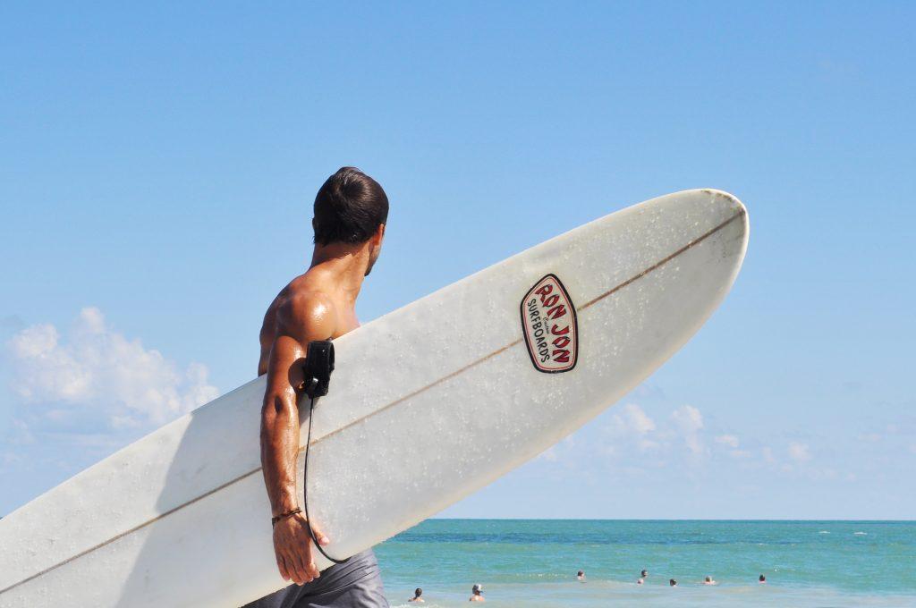 Surfer mit Brett in der Hand und Blick auf Strand von Florida