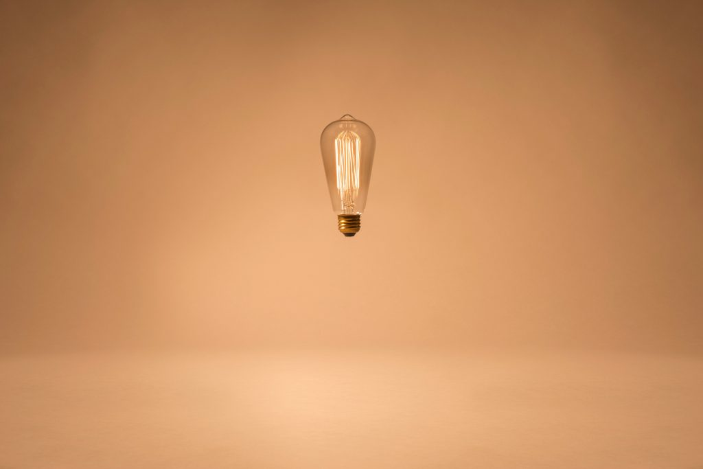 Schwebende Edison Birne vor Caramelfarbenen Hintergrund