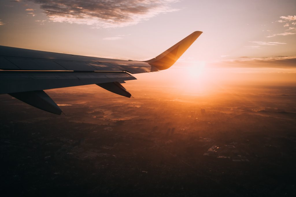 Fensterblick aus dem Flugzeug mit Blick auf untergehende Sonne