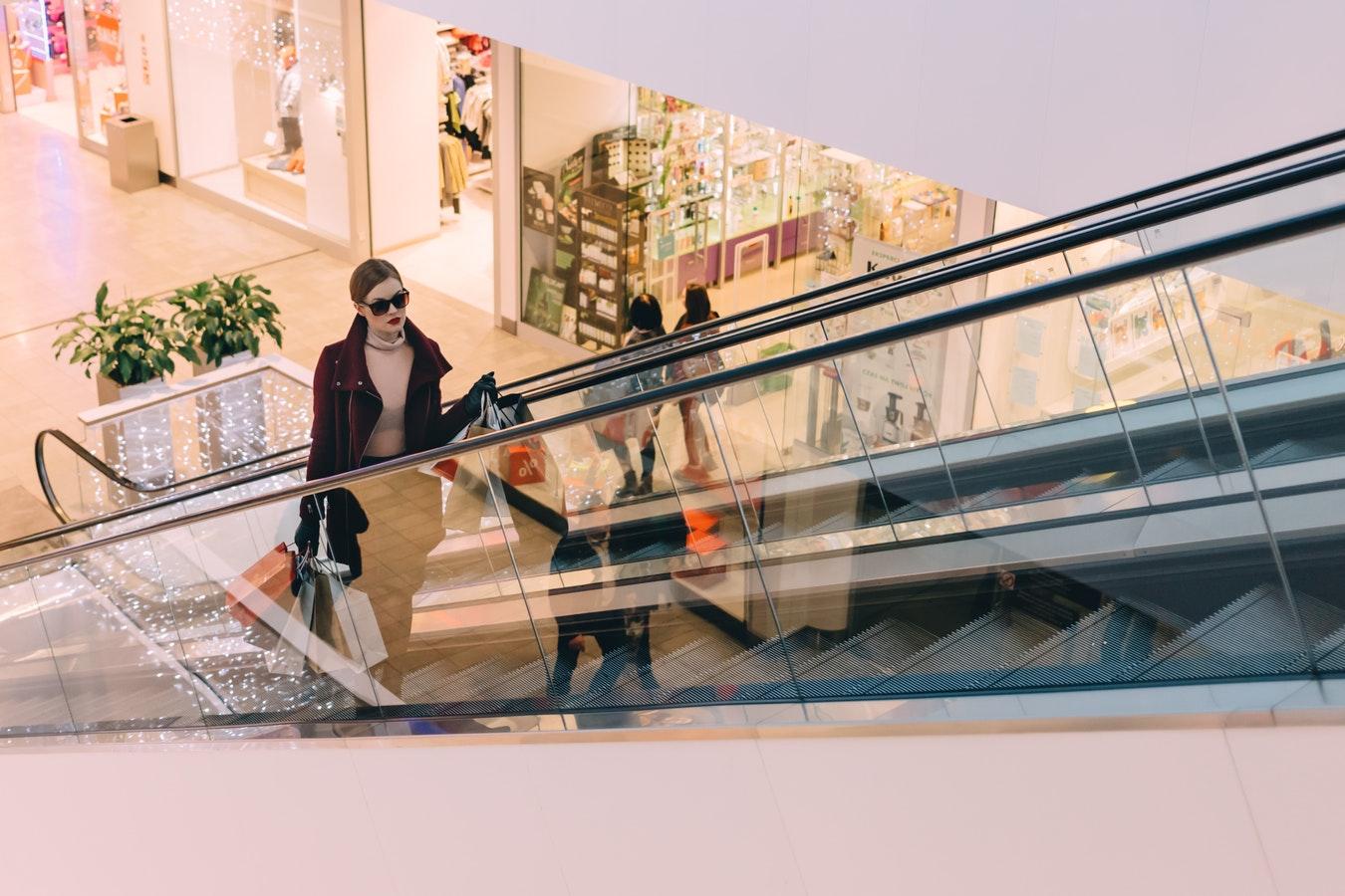 Frau auf Rolltreppe in Shoppingmall
